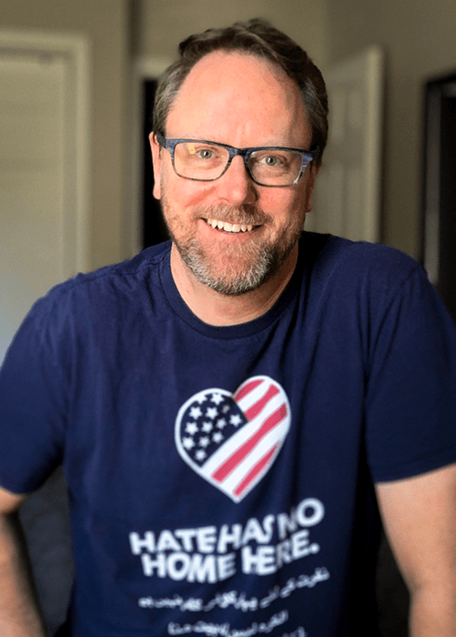 "Picture of a bearded Steve, smiling, wearing blue-rimmed eyeglasses, and a navy blue T-shirt with a heart that has part of the American Flag inside it, and below, it says, ""Hate has no home here."""