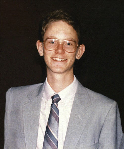 Picture of Steve smiling as a young boy, wearing a light grey suit, white button down shirt, lavender, grey, and pink diagonally striped tie, and large brown rimmed eyeglasses.